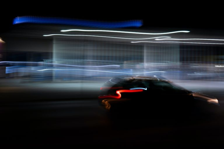 Night time shot of car with streaming lights